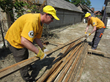 Scientology Volunteer Ministers stack beams salvaged from a condemned home in the village of Kopanica, in Bosnia and Herzegovina. These can be used to help the family rebuild their home.