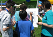 Youth sign a drug-free pledge at a drug education and prevention booth
