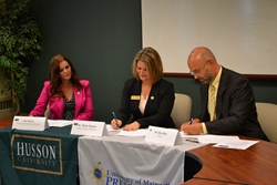 Taking part in the signing event are, from left, Jen Flynn, Husson's Presque Isle Campus Director; Dr. Marie Hansen, Husson's College of Business Dean; and Dr. Ray Rice, UMPI's Provost.