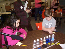 """Students observing the properties of a liquid in bottles before investigating them in last year's funded project project 'Lesson Study."""""""