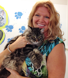 A rescued cat waiting to be adopted at the Winnipeg Humane Society is held by Aileen White, Director of Communications
