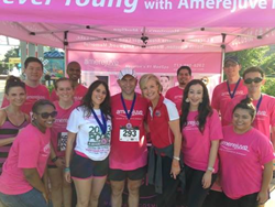 The Amerejuve team, dressed in pink shirts under a pink Amerejuve shirt, smiling as a group at the 2013 Amerejuve PCOS 5k Fun Run and Walk.
