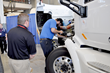 A competitor investigates a bug on a brand new Peterbilt truck on the HVAC station