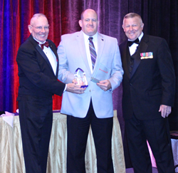 Gene Overstreet (left), 12th Sergeant Major of the Marine Corps and a Young Marines board member, with Mike Kessler (right), national executive director and CEO of the Young Marines, present Scott Riley with the National Adult Volunteer of the Year award.