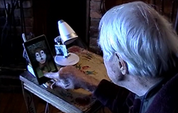 Photo of an older adult with Alzheimer's engaging with a GeriJoy caregiver through a tablet-based avatar.