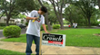 Son Nicholas Flores posts a campaign sign while his brother, sister and father blockwalk the neighborhood.