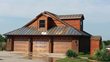 A copper garage door and gutters sets off this mixed-texture home exterior featuring a DaVinci polymer shake roof.