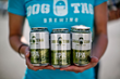 Katy Jordan, Marketing Director at Dog Tag Brewing, holds a six-pack of their IPA.
