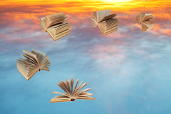 Books fly over blue and yellow sunset clouds