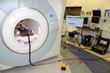 An overview of the MRI-compatible prostate biopsy robotic system. From left, the robot in place inside the MRI unit; the foot pedal the physician used to activate the robot; a screen that display's th