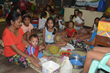 Sponsored child Kristine (center, holding a green bowl) has a meal with her family at an evacuation center.