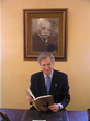 Michel Escoffier seated in front of a photo of his Great Grandfather Master Chef Auguste Escoffier