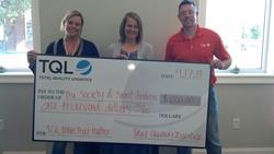 TQL Nashville employees present donation as part of Moves that Matter program.