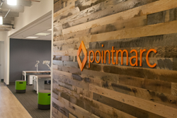 Pointmarc's new entrance features reclaimed wood walls and a sneak peek of the new branding.
