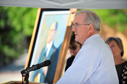 Former SLCC President Jay L. Nelson's son Bruce Neslon speaks at the dedication of the college's quad at its Taylorsville Redwood Campus, with a portrait of his late father in the background.