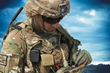 Soldier in the field using multiple electronic devices that require power.