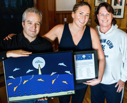 Artist John Kraft presents Dolphin Detour to Kim Chambers