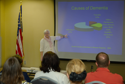 Presenter during the 2013 seminar. Audience is looking at presenter who is pointing to a PowerPoint slide titled Cause of Dementia that has a pie chart with the different causes and percentages.