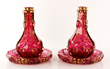 """19th century pair cranberry Bohemian glass carafes, with matching under plates, blown and cut glass, with gilt decoration, made for the Islamic market, 9 3/4"""" dia under plates, 10 3/4"""" h carafes."""