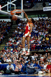 Picture shows Spud Webb slam dunking in front of a crowd.
