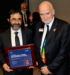 ICTP Director Fernando Quevedo (at left) accepts a commemorative plaque and congratulations from SPIE CEO Eugene Arthurs during the center's 50th anniversary celebration.
