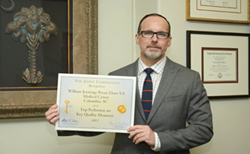 Medical Center Director Timothy McMurry holding 2013 Joint Commission Top Performer Certificate. Photo: Ken Holt