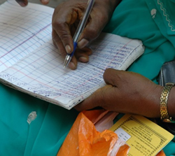 A microfinance client enters a payment into her notebook