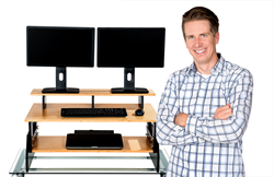 Zerwas is shown here standing (of course) next to one of his sleek new StandingDeskToppers which converts any regular desk into an ergonomically correct standing desk.