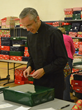 Fr. Kevin Baldwin, LC, Chaplain at Everst Academy in Lemont, wraps a gift box preparing for the Community Christmas Bash.