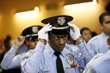 LAPD Cadet Commander adjusts his hat at the LAPD Cadet Program graduation, partly funded by $1.5M in grants from the Ray Charles Foundation.