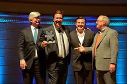 Mark Cleveland holds the NEXT Entrepreneur of the Year trophy. Presenters are John Stein–Bank of America, Michael Burcham–Nashville Entrepreneur Center, Ralph Schulz – Nashville Chamber of Commerce.