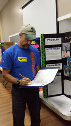 Certified Arborist Rob Calley judges middle school science fair project.