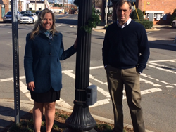 Maggie Collister and Tobe Holmes from Charlotte Center City Partners stand at a busy intersection where they are conducting pedestrian counts for foot traffic analysis.