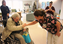 One of the first residents at Venetian Care & Rehab Center, Larry Weghorn, is greeted by his  care partner Ayde Ruiz today as VP Batsheva Katz, and Administrator Gina Kirchoff look on.