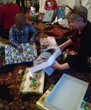 Abernethy Laurels Resident Barbara Murray helping children open their gifts