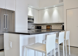 The tall upper wall white melamine cabinets in the kitchen