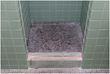 Typical college shower where the tile walls and shower pan are in need of an update