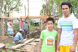 Brothers James and Cyrus stand outside of their new house being built with help from Unbound after Typhoon Haiyan destroyed their home in 2013.