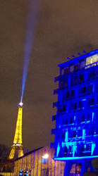 The Eiffel Tower provides emphasis to a light artwork on the UNESCO headquarters building celebrating the International Year of Light.