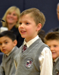 An Everest Academy first grader smiles at his success in hearing he has correctly spelled his given word in the Annual Spelling Bee Academic Competion