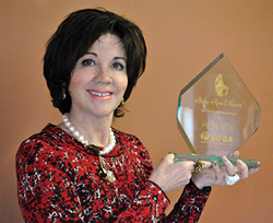 Kerry McCoy poses with the Betsy Ross Award presented to her by the National Independent Flag Dealers Association.