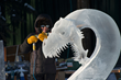 Steve Brice carves a dragon head from a block of ice. (Photo by Sherman Hogue/Explore Fairbanks)