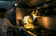 February 10, 2015, Boston, Massachusetts: A chef cooks as flames rise into a newly installed Eco Thermal Filter System in the kitchen of The Stockyard Steakhouse restaurant in Brighton, Massachusetts