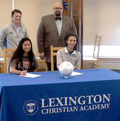 Girls Varsity Head Coach, Ryan Patrie (left),  and Head of School, Tim Russell (right), celebrate with Abigail Bridge (left bottom) and Kesha Porter (right bottom) as they sign their National Letters of Intent