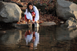 Kara Martin, Eastern Band of Cherokee Indians citizen, scoops water from the Oconaluftee River.