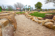 Naturalized play elements, like this dry creek bed, provide opportunities for children to explore and discover the natural surroundings.