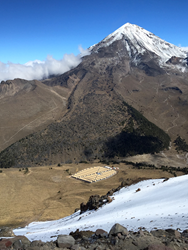This view of the HAWC observatory was taken from the slopes of Volcan Sierra Negra. Its neighbor, Pico de Orizaba, the highest peak in Mexico, is visible in the background. Photo: HAWC Collaboration