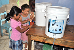 Two Compassion-sponsored children in Honduras pour clean drinking water from a Water of Life filter