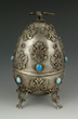 Russian silver egg, with turquoise and amethyst cabochons, opens to reveal figure of peasant with basket that opens on his back, possibly a spice box, exterior decorated all over with double-headed ea