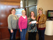 WCCTA representative Marcie Boerner presents check to Candy Bilstad, Colleen Goodwin and Judy Harvey